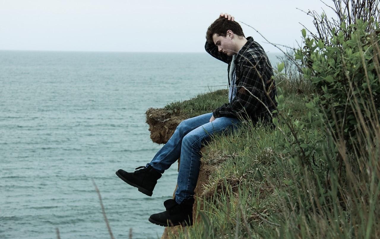 崖の上で悩んでいる男性の写真