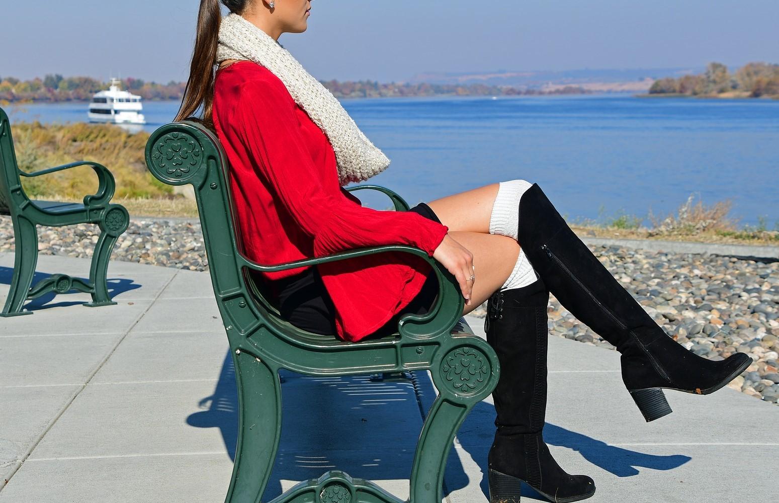 赤いコートを着て椅子に座るモデルスタイルの美しい女性